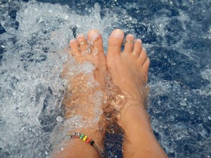 Dangling feet in the water behind the boat